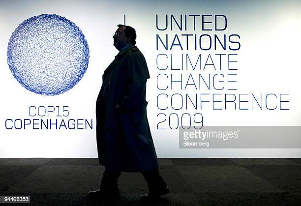 A delegate walks past a sign at the entrance to the COP15 United Nations Climate Change Conference at the Bella Centre in Copenhagen Denmark on...