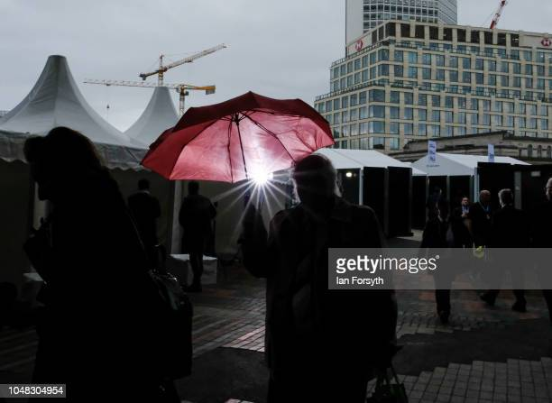 A delegate walks through rain as they enter the International Convention Centre on day three of the Conservative Party Conference on October 2 2018...