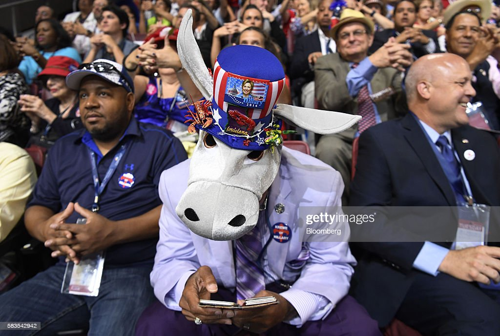 A delegate wearing a donkey hat checks a mobile device during the Democratic National Convention (DNC) in Philadelphia, Pennsylvania, U.S., on Tuesday, July 26, 2016. Democrats began their presidential nominating convention Monday with a struggle to fully unite the party, following a dramatic day of internal squabbling and protests. Photographer: David Paul Morris/Bloomberg via Getty Images