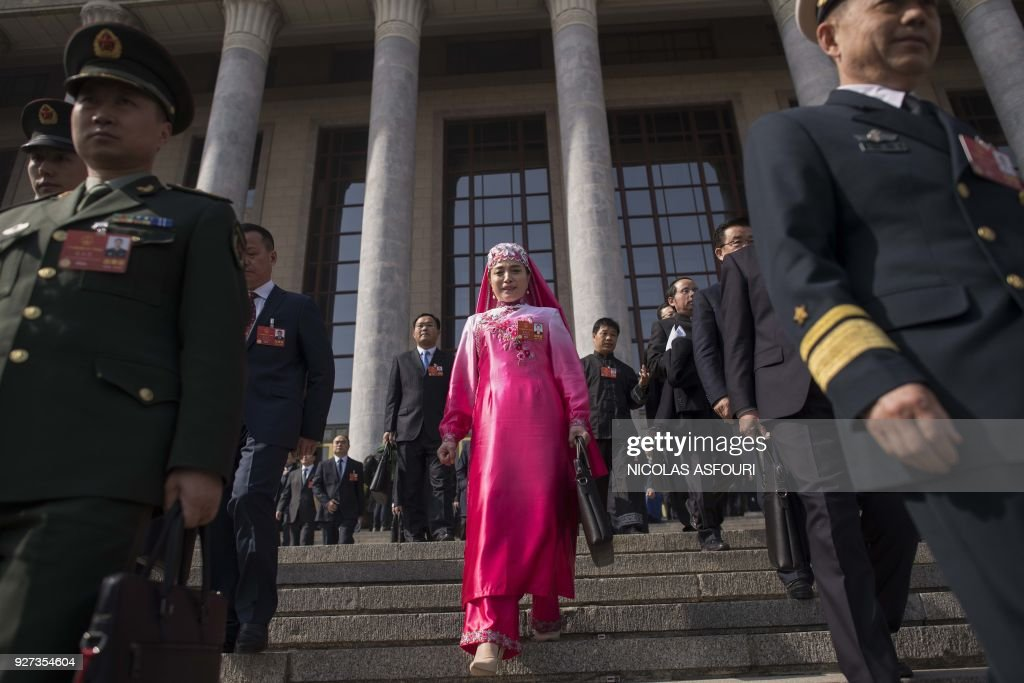 TOPSHOT - A delegate (C), wearing an ethnic minority outfit, and military delegates (L-R) leave the Great Hall of the People after the opening session of the National People's Congress, China's legislature, in Beijing on March 5, 2018. Thousands of Chinese legislators erupted into enthusiastic applause over plans to give President Xi Jinping a lifetime mandate to mould the Asian giant into a global superpower. /