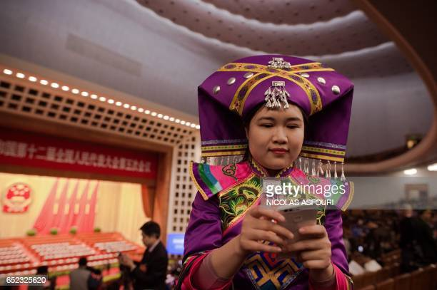 Delegate wearing an ethnic minority outfit looks at her smartphone before the third plenary Session of the fifth session of the 12th National...