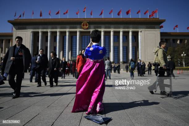 Delegate wearing an ethnic minority outfit takes a picture after the third plenary session of the National People's Congress outside the Great Hall...