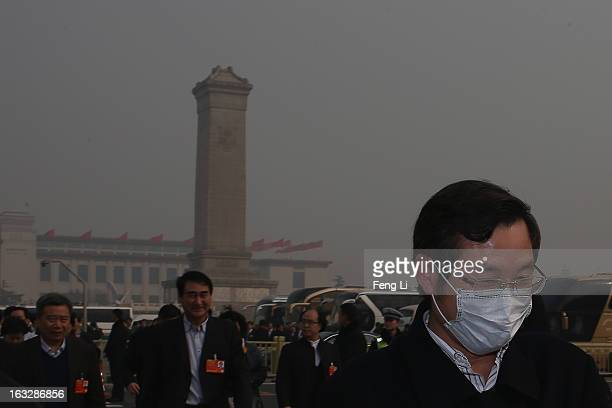 Delegate wearing the mask walks to the Great Hall of the People before a plenary session of the Chinese People's Political Consultative Conference...