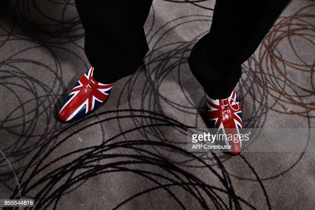 A UKIP delegate wearing Union flagthemed shoes attends the first day of the UK Independence Party National Conference in Torquay southwest England on...
