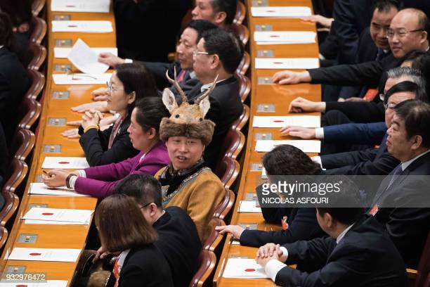 A delegate with an ethnic minority costume looks on at the end of the fifth plenary session of the first session of the 13th National People's...