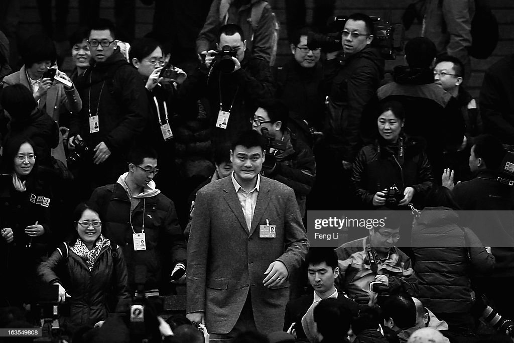 Delegate Yao Ming (C), a former NBA basketball star, walks through a swarm of journalists outside Great Hall of the People after attending the closing session of the annual Chinese People's Political Consultative Conference (CPPCC) on March 12, 2013 in Beijing, China. The newly-elected Chairman of the CPPCC Yu Zhengsheng pledged Tuesday that China will not copy Western political systems under any circumstances.