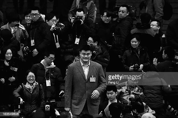 Delegate Yao Ming a former NBA basketball star walks through a swarm of journalists outside Great Hall of the People after attending the closing...