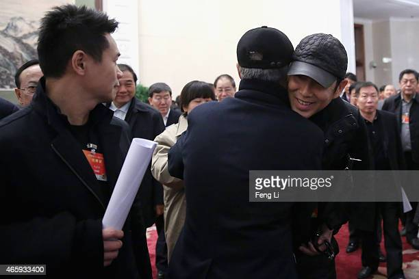 Delegate Zhao Benshan hugs with delegate Chen Daoming as they leave the Great Hall of the People after the third plenary session of China's...