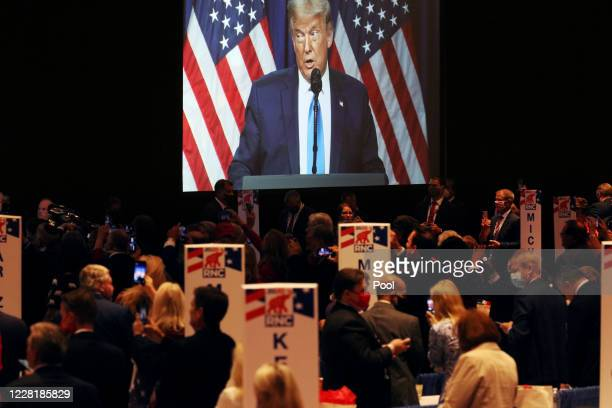 Delegates and RNC staff listen as President Trump speaks on the first day of the Republican National Convention at the Charlotte Convention Center on...