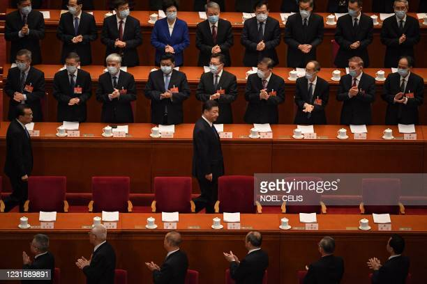 Delegates applaud as China's President Xi Jinping and Premier Li Keqiang arrive for the second plenary session of the National Peoples Congress at...