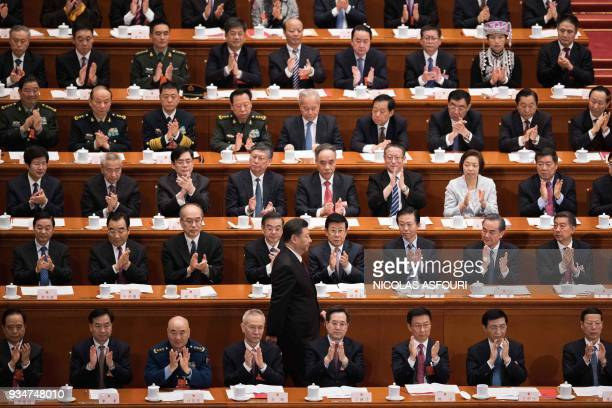 Delegates applaud as China's President Xi Jinping walks past after he delivered a speech during the closing session of the National People's Congress...