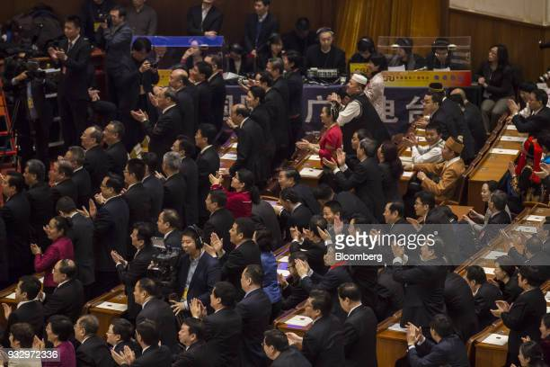 Delegates applaud during a session at the first session of the 13th National People's Congress at the Great Hall of the People in Beijing China on...