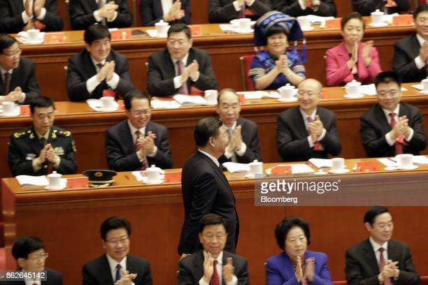 Delegates applaud Xi Jinping, China's president, as he returns to his chair after delivering his speech at the opening of the 19th National Congress...