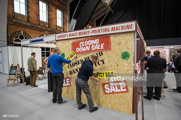 Delegates apply bankruptcy sale stickers to stand with the sign 'Labour's Magic MoneyPrinting Machine' above it at the Conservative Party's annual...
