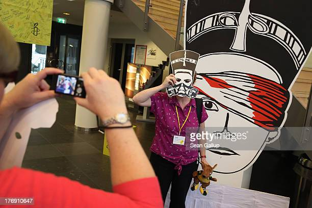 Delegates at a meeting of Amnesty International photograph one another holding up masks that depict ancient Egyptian Queen Nefertiti wearing a gas...