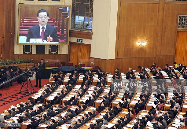 Delegates attend as the huge screen showing the image of Chinese President Hu Jintao during the second plenary session of of the National People's...