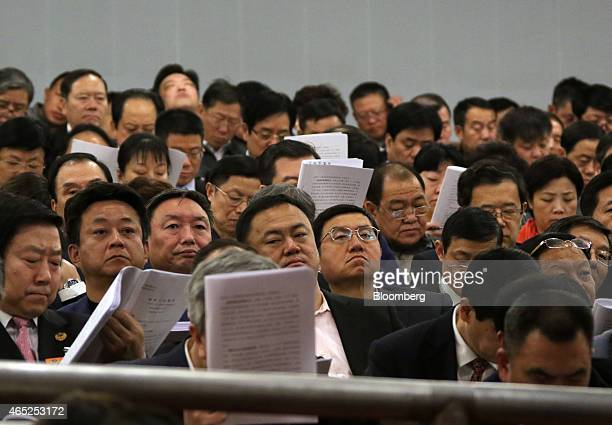 Delegates attend the opening of the third session of the 12th National People's Congress at the Great Hall of the People in Beijing China on Thursday...