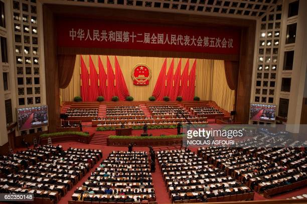Delegates attend the third plenary session of the fifth session of the 12th National People's Congress at the Great Hall of the People in Beijing on...