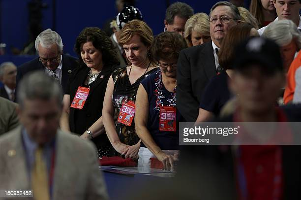 Delegates bow their heads during the pledge of allegiance at the Republican National Convention in Tampa, Florida, U.S., on Wednesday, Aug. 29, 2012....