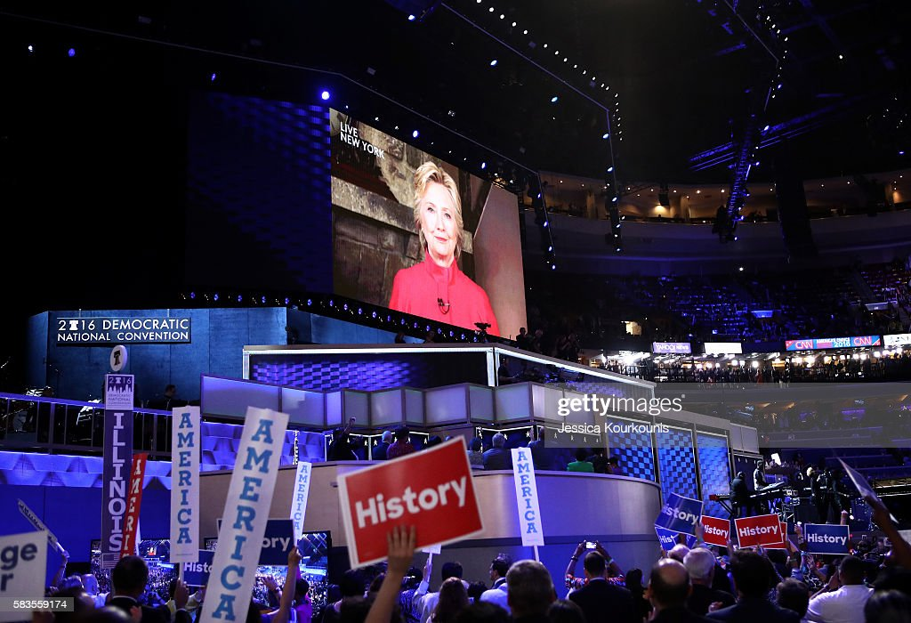 Delegates cheer as a screen displays Democratic presidential candidate Hillary Clinton delivering remarks to the crowd during the evening session on the second day of the Democratic National Convention at the Wells Fargo Center, July 26, 2016 in Philadelphia, Pennsylvania. Democratic presidential candidate Hillary Clinton received the number of votes needed to secure the party's nomination. An estimated 50,000 people are expected in Philadelphia, including hundreds of protesters and members of the media. The four-day Democratic National Convention kicked off July 25.