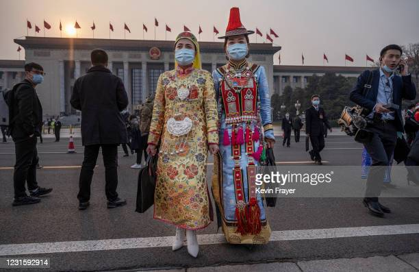 Delegates dressed in traditional costume leave following the second plenary session of the National People's Congress at the Great Hall of the People...