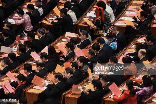 Delegates examine their ballots during the sixth plenary session of the National People's Congress at the Great Hall of the People on March 18 2018...