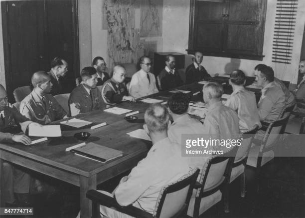 Delegates from Japan and the United States discuss the former's terms of surrender in a conference room at General MacArthur's headquarters Manila...