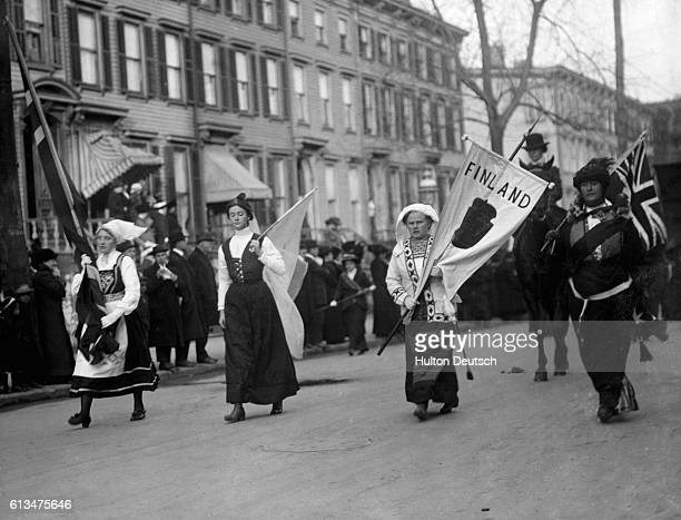Delegates from Sweden and Finland in traditional dress carry banners in a suffragettes parade through the streets of Brooklyn