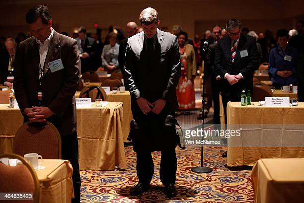 Delegates from the Republican National Committee bow their heads in prayer before the start of the annual RNC winter meeting January 24 2014 in...