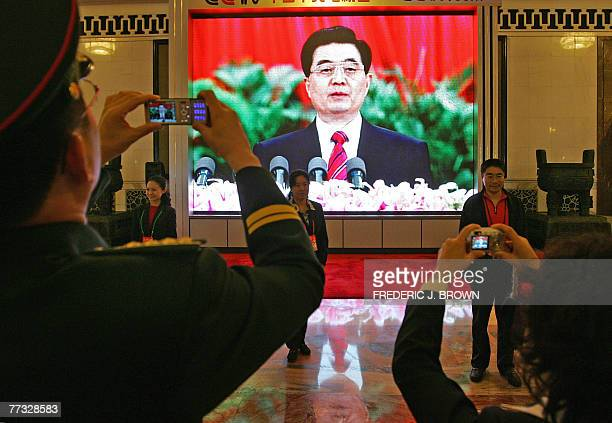 Delegates have their picture taken in front of a large screen televising Chinese President Hu Jintao's speech at the opening session of the ruling...