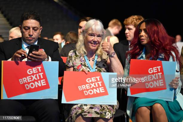 """Delegates hold """"Get Brexit Done"""" posters during the first day of Conservative Party Conference at Manchester Central on September 29, 2019 in..."""