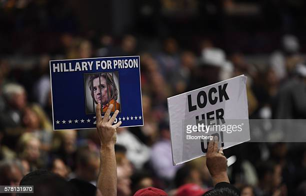 Delegates hold signs reading 'Hillary For Prison' and 'Lock Her Up' during the Republican National Convention in Cleveland Ohio US on Wednesday July...