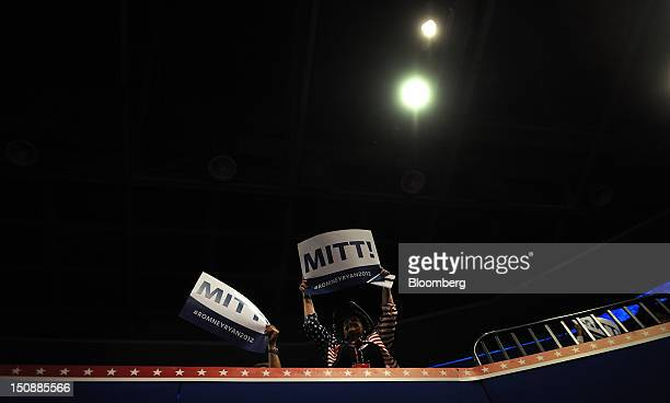Delegates hold up Mitt Romney signs at the Republican National Convention in Tampa Florida US on Tuesday Aug 28 2012 Delegates are gathered in Tampa...