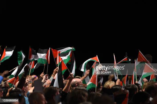 Delegates hold up Palestinian flags during a debate on the third day of the Labour party conference in Liverpool north west England on September 25...