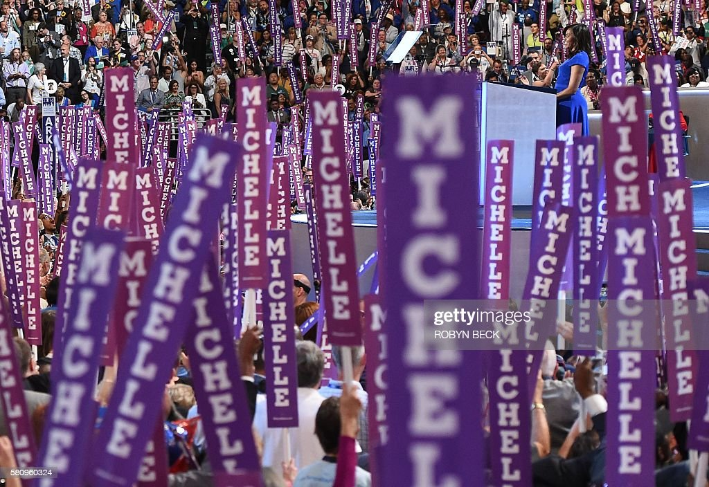 TOPSHOT - Delegates hold up signs supporting US First Lady Michelle Obama gestures during Day 1 of the Democratic National Convention at the Wells Fargo Center in Philadelphia, Pennsylvania, July 25, 2016. / AFP / Robyn BECK