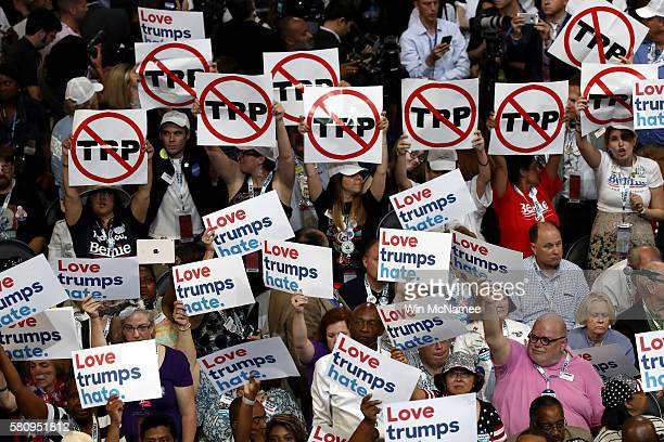 Delegates hold up signs that read 'TransPacific Partnership ' and 'Love trumps hate' during the opening of the first day of the Democratic National...