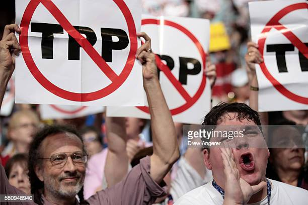Delegates hold up signs that read 'TransPacific Partnership ' on the first day of the Democratic National Convention at the Wells Fargo Center July...