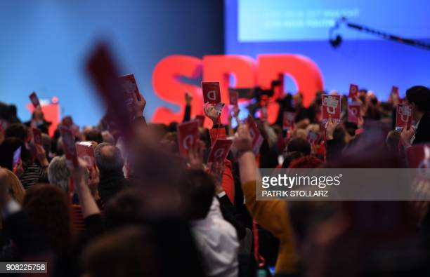 Delegates hold up their voting cards during an extraordinary party congress of Germany's social democratic SPD party in Bonn western Germany on...