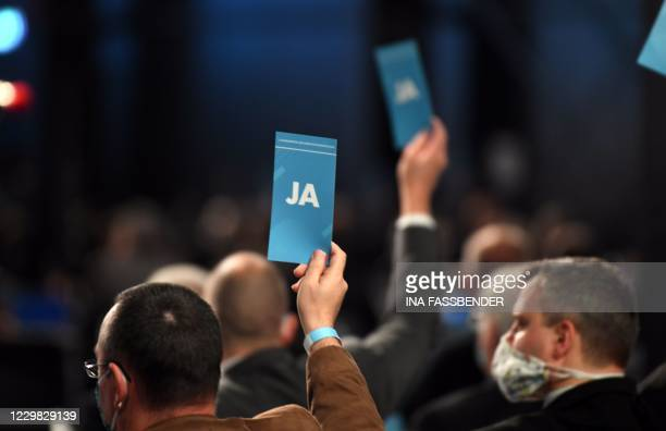 Delegates hold up their voting cards during the Party Congress of farright AfD party at the Wunderland Kalkar, western Germany, on November 28, 2020.