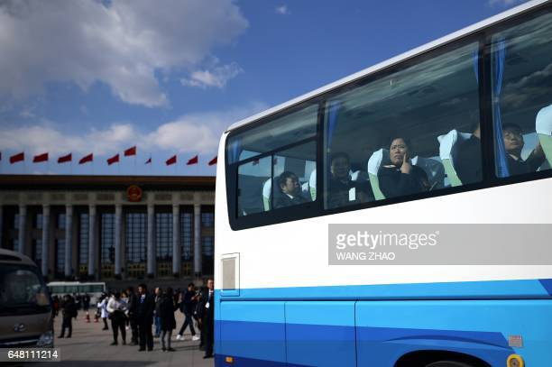 Delegates leave the Great Hall of the People by bus after the opening session of the National People's Congress China's legislature in Beijing's...