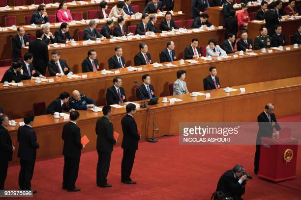Delegates line up to vote during the fifth plenary session of the first session of the 13th National People's Congress at the Great Hall of the...