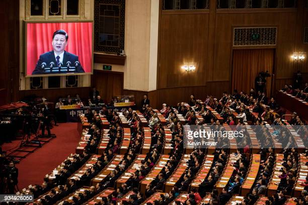 Delegates listen to a speech by China's President Xi Jinping as he is seen on a large screen during the closing session of the National People's...