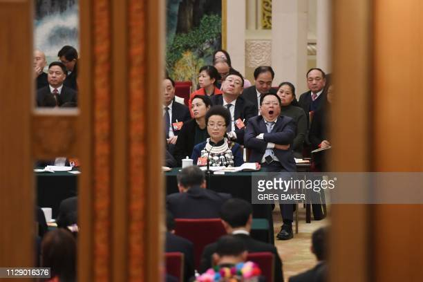 Delegates listen to speeches during a meeting of the Hunan delegation in the Hunan hall of the Great Hall of the People during the ongoing National...