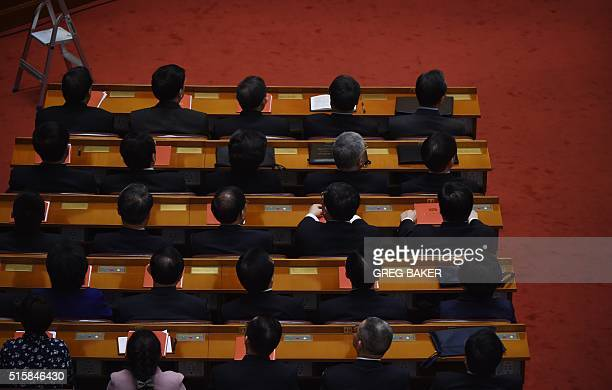 Delegates listen to speeches during the closing session of the National People's Congress in the Great Hall of the People in Beijing on March 16 2016...