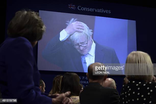 Delegates look at a big screen showing British Conservative party member of parliament and London Mayor Boris Johnson giving his speech on the third...