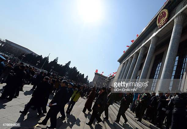 NPC delegates make their way down the steps of the Great Hall of the People after the opening session of the 12th National People's Congress in...