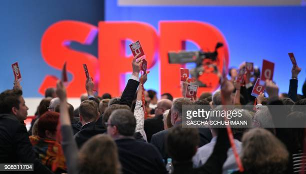 Delegates of Germany's social democratic SPD party hold up their voting cards during an extraordinary SPD party congress in Bonn, western Germany, on...