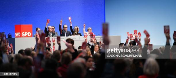 Delegates of Germany's social democratic SPD party hold up their voting cards during an extraordinary SPD party congress in Bonn western Germany on...