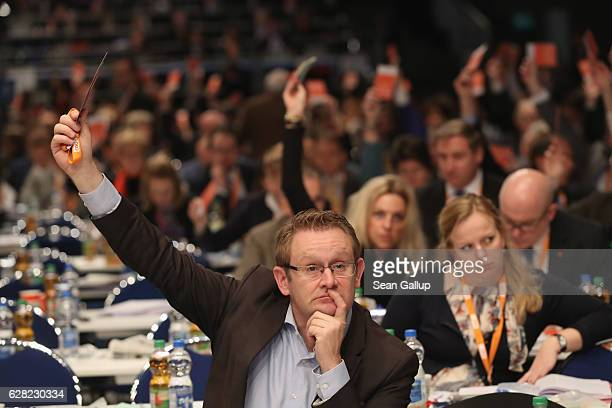 Delegates of the German Christian Democrats hold up their voting cards while voting on a measure at the 29th federal congress of the CDU on December...