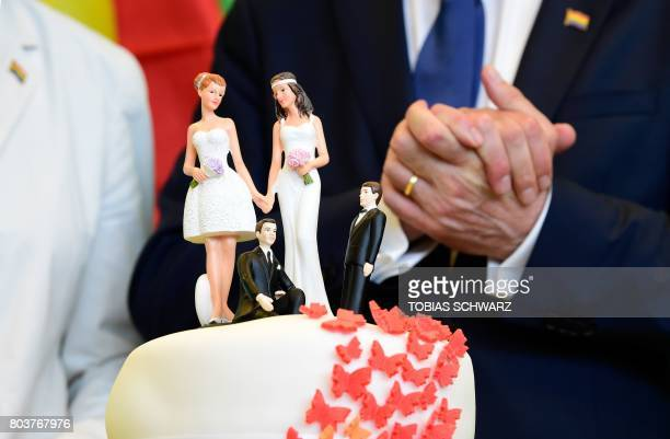 Delegates of the Greens stand behind a wedding cake decorated with figurines of two women and two men at the offices of the Greens' parliamentary...